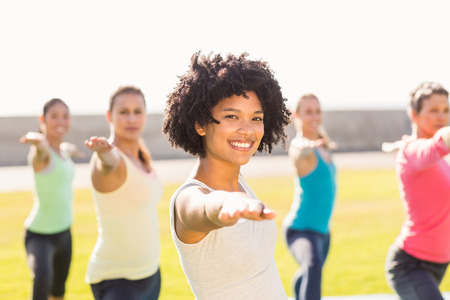 mid adult women: Portrait of smiling sporty woman doing yoga in yoga class in parkland Stock Photo