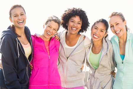 people laughing: Portrait of laughing sporty women with arms around each other in parkland Stock Photo