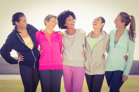 parkland: Laughing sporty women with arms around each other in parkland