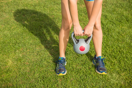 parkland: Sporty woman exercising with kettlebell in parkland Stock Photo