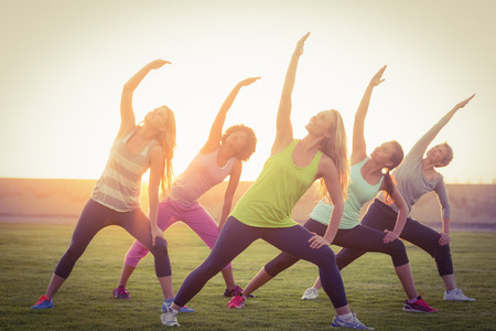 parkland: Sporty women warming up during fitness class in parkland Stock Photo