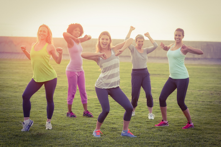 parkland: Portrait of happy sporty women dancing during fitness class in parkland