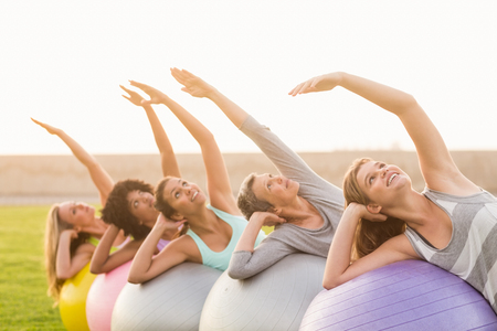 women working out: Smiling sporty women working out with exercise balls in parkland