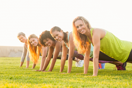 camp: Portrait of smiling sporty women doing push ups during fitness class in parkland