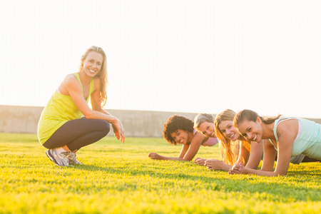 planking: Portrait of smiling sporty women planking during fitness class in parkland Stock Photo