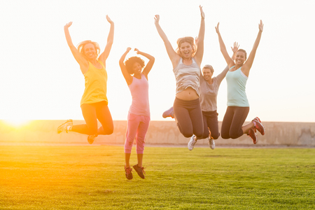 slender woman: Portrait of happy sporty women jumping during fitness class in parkland Stock Photo