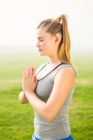 slender woman: Peaceful sporty blonde meditating in parkland