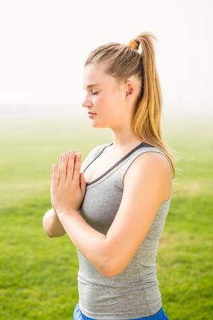 mooie vrouwen: Vreedzame sportieve blonde mediteren in een park