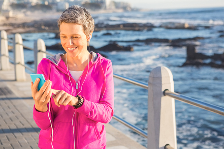 Smiling sporty woman enjoying music and holding phone at promenade