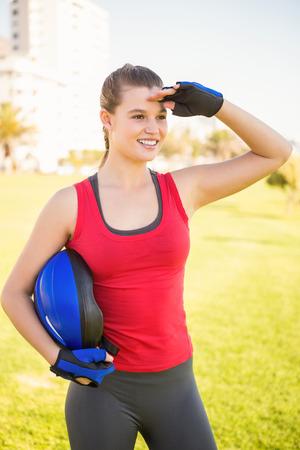 blading: Smiling sporty blonde holding helmet at promenade