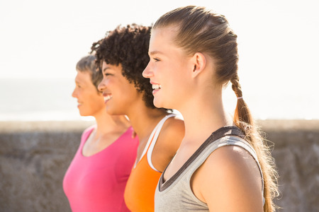 far away: Smiling sporty women looking far away at promenade Stock Photo