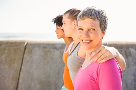 mujeres maduras: Retrato de la mujer sonriente deportiva con dos amigos en el paseo marítimo Foto de archivo
