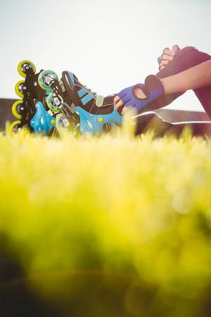 blading: Woman wearing inline skates sitting in grass at promenade Stock Photo