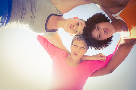 50s women: Portrait of sporty women with arms around posing down to camera at promenade