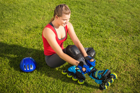 blading: Smiling sporty blonde skater sitting in grass at promenade Stock Photo
