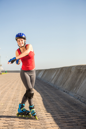 blading: Portrait of carefree sporty blonde posing with inline skates at promenade