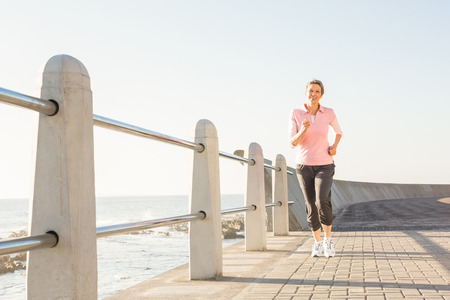 mature adult: Smiling sporty woman jogging at promenade on a sunny day Stock Photo