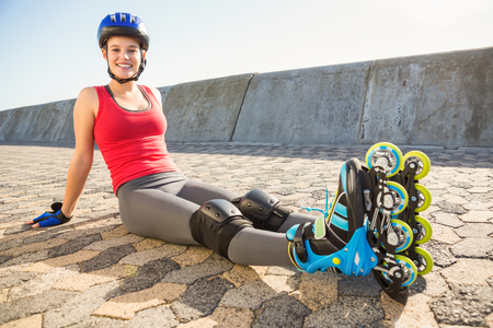 Portrait of smiling sporty blonde skater sitting on ground at promenade Stock Photo