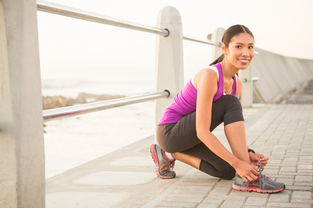 Portrait of smiling fit woman tying shoelace at promenade on a sunny day