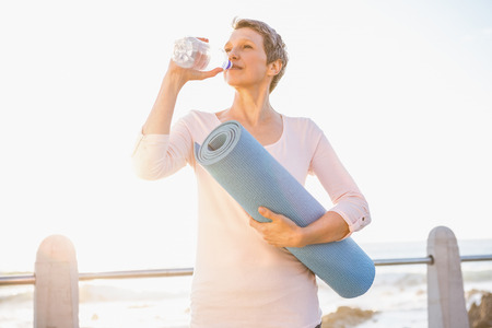 yoga mat: Sporty woman with exercise mat drinking water at promenade