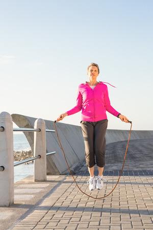 saltar la cuerda: Mujer deportiva que salta en el paseo en un día soleado Foto de archivo
