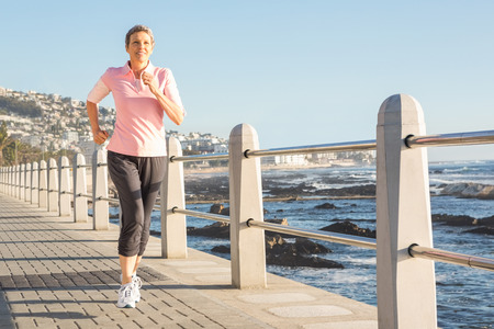 woman working out: Sporty woman jogging at promenade on a sunny day Stock Photo