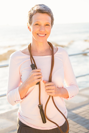 skipping rope: Portrait of smiling sporty woman with skipping rope at promenade