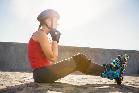 fastening: Sporty blonde skater sitting on ground and fastening helmet at promenade Stock Photo