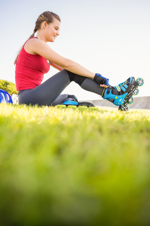 blading: Smiling sporty blonde skater sitting in grass at promenade Stock Photo