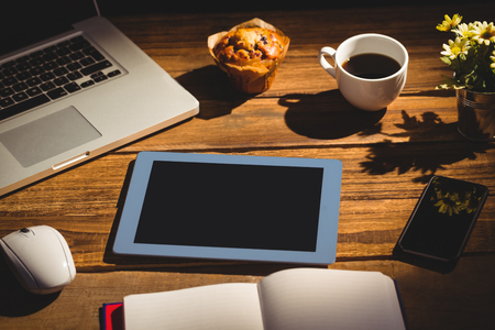 books on a wooden surface: View of a desk with electronic devices Stock Photo