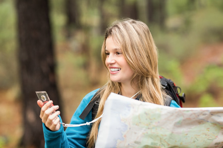 compass: Young pretty hiker using compass and map in the nature Stock Photo