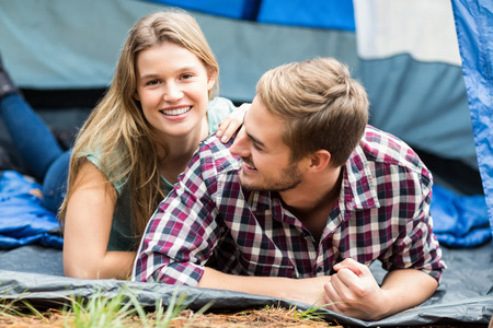 adventuring: Young pretty hiker couple lying in a tent in the nature Stock Photo