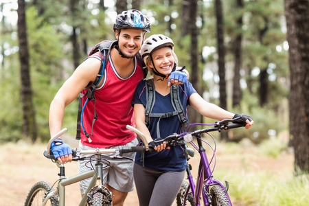 adventuring: Happy young biker couple looking at camera in the nature