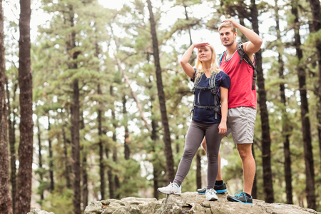 adventuring: Young happy hiker couple looking away in the nature