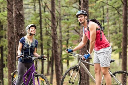 adventuring: Young happy couple on bikes looking away in the nature Stock Photo