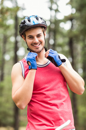 adventuring: Handsome young biker looking at camera in the nature
