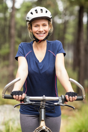 adventuring: Young pretty happy biker looking at camera in the nature Stock Photo