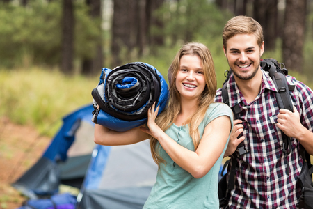 sleeping bag: Portrait of a young pretty hiker couple holding a sleeping bag and backpack in the nature