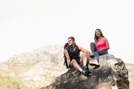Young happy joggers sitting on rock in the nature