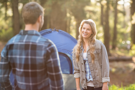 adventuring: Happy young camper couple looking at each other in the nature