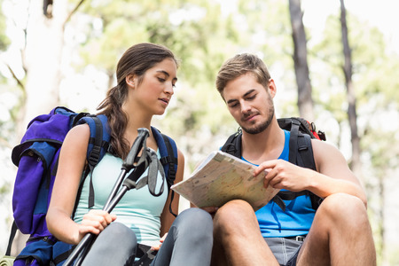joggers: Young happy joggers looking at map in the nature Stock Photo