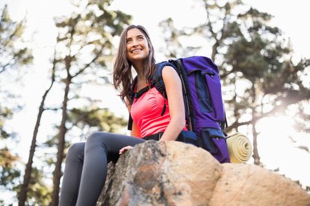 adventuring: Young happy jogger sitting on rock and looking away in the nature Stock Photo