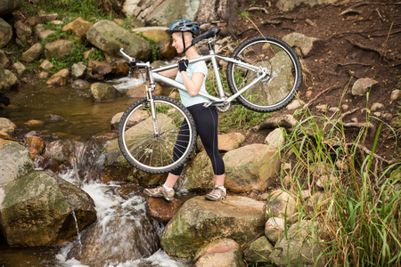 profile view: Profile view of a fit woman lifting her bike and crossing a river
