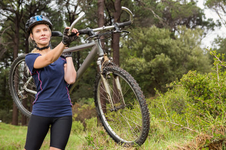 cross street with care: Athletic blonde carrying her mountain bike in the nature Stock Photo