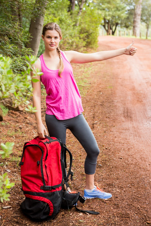 hitchhiking: Pretty blonde with backpack hitchhiking in the nature