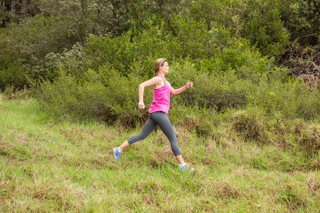 cross street with care: Pretty blonde athlete jogging in the nature