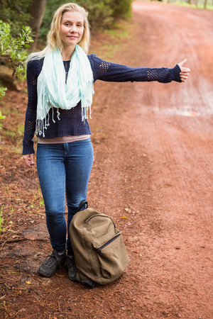 adventuring: Portrait of a pretty hitchhiker sticking thumb out on a crossing path