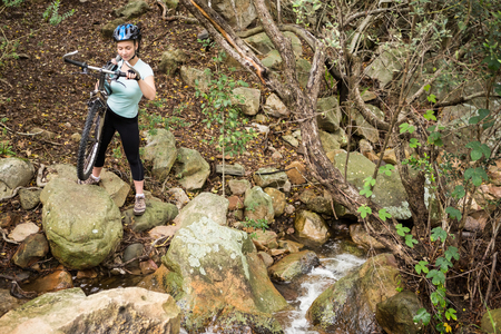 adventuring: Smiling fit woman lifting her bike while crossing a rock path Stock Photo