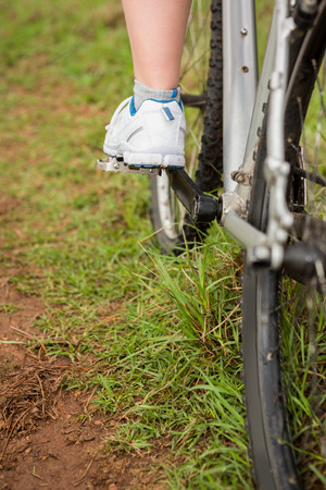 escapism: Close up view of woman pedaling on mountain bike in the nature Stock Photo