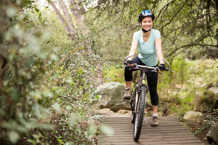 adventuring: Smiling fit woman taking a break on her bike on a wooden path